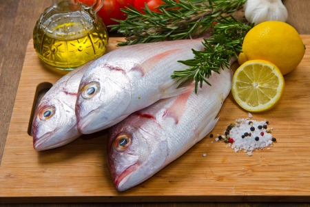 a group of sea bream with lemon and rosemary on wood table Stock Photo