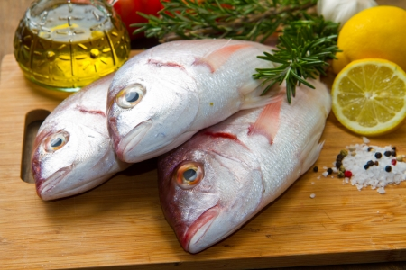 a group of sea bream with lemon and rosemary on wood Stock Photo - 17842721