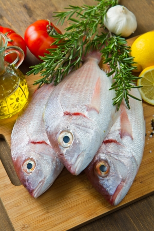 fish market: a group of sea bream with lemon and rosemary on wood table Stock Photo