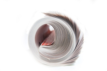 Rolled up magazine on white photo