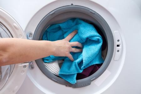 lavadora con ropa: A cerca de una máquina de lavado cargada con ropa aislados en el fondo blanco