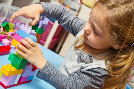 Little girl is playing with building bricks  photo