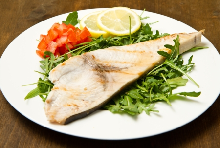 pez espada: pez espada asado con lim�n, ensalada y tomates en el fondo de madera
