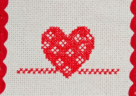 red stitches: red heart embroidered in cross stitch on  canvas