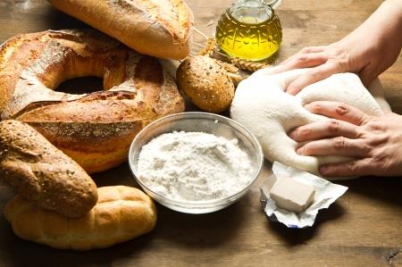 amasando: manos femeninas en masa de harina en la mesa de amasar closeup