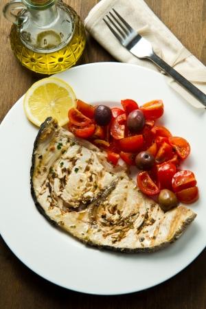 pez espada: pez espada con tomate y limón en la madera