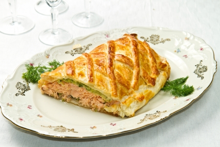 Traditional salmon in puff pastry with spinach and zucchini Standard-Bild