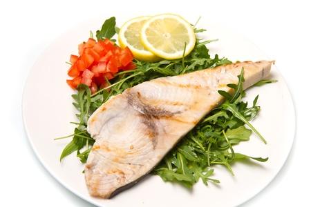 pez espada: pez espada asado con limón, ensalada y tomates en un plato blanco Foto de archivo