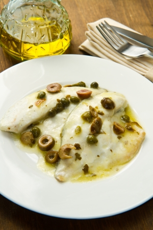 bass fish: sea bream fillet with green olives and capers Stock Photo