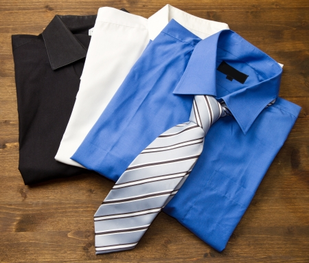 Close up of stacked shirts with tie on wood photo