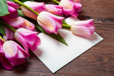 bouquet of pink tulips and postcard on wood photo