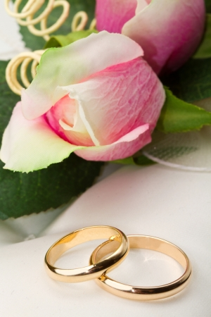 wedding rings and pink roses on white background photo