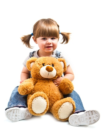 adorable toddler girl hugging a teddy bear Фото со стока