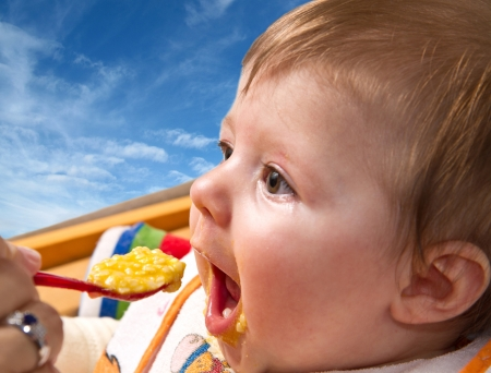 eat smeared: pretty baby girl eating from spoon                Stock Photo
