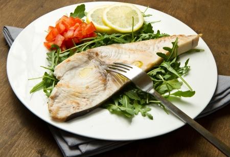 pez espada: pez espada asado con lim?n, ensalada y tomates en el fondo de madera