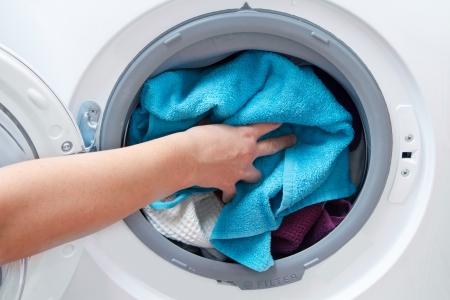 lavadora con ropa: A cerca de una m?quina de lavado cargada con ropa aislados en el fondo blanco