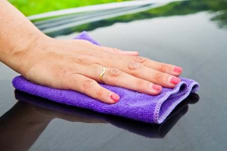 A Hand drying a back car with a synthetic  cloth Stock Photo