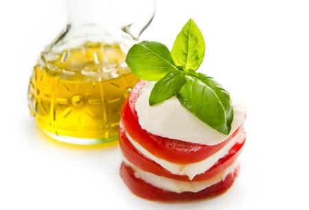 Tomato and mozzarella with basil leaves on white Stock Photo - 20886184