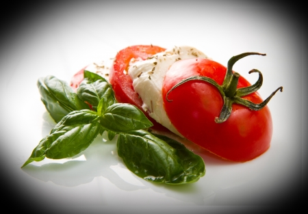 Tomato and mozzarella with basil leaves on white Stock Photo - 20886188