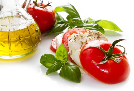 Tomato and mozzarella with basil leaves on white Stock Photo - 20886190
