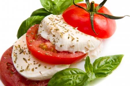 Tomato and mozzarella with basil leaves on white  Stock Photo - 20886193