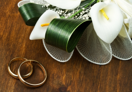 Wedding rings with calla bouquet on wooden background photo