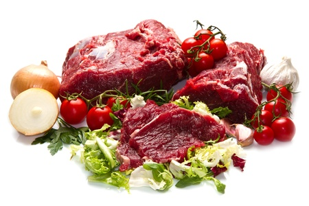 butchered: huge red meat chunk with vegetables isolated over white background