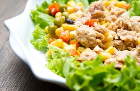 mais: tuna salad with mais on white shell dish isolated on wood