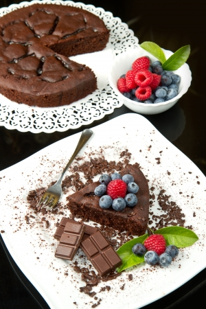 chocolate cake with fresh berry on white dish and black background photo