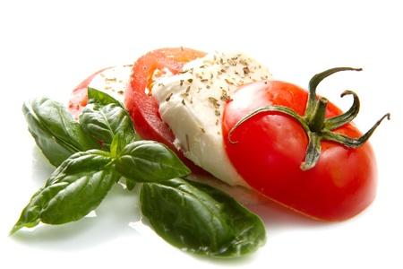 Tomato and mozzarella with basil leaves on white  Stock Photo - 21378361