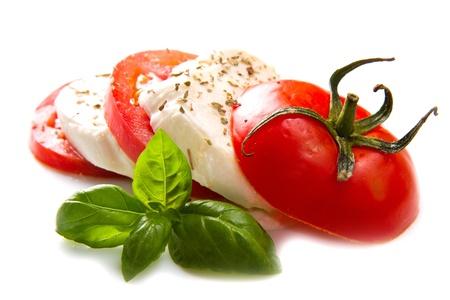 mozzarella cheese: Tomato and mozzarella with basil leaves on white  Stock Photo