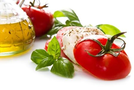 Tomato and mozzarella with basil leaves on white Stock Photo - 21378364