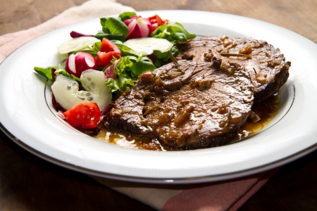 meatloaf:  beef  garnished with fresh salad,  tomatoes, raddishes and cucumbers Stock Photo