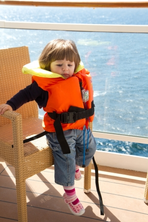 little girl dressed in life jacket stands  in  cabins balcony  of ship  photo