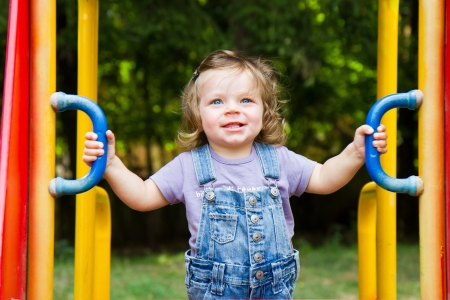 Happy smiling child  playing in a  playground area  photo