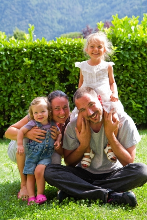Portrait of happy family on the green lawn photo