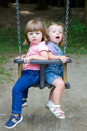 Happy little girls swinging in a park  photo