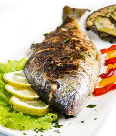 gilt head: Grilled gilt head sea bream on plate with lemon salad and grilled vegetables