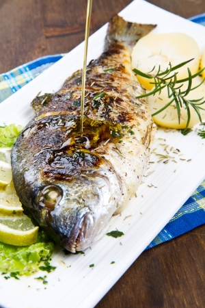 cooked fish: Grilled gilt head sea bream on plate with lemon and rosemary and potatoes  Stock Photo