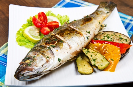 grilled fish: fish, sea bass grilled with lemon and grilled vegetables Stock Photo