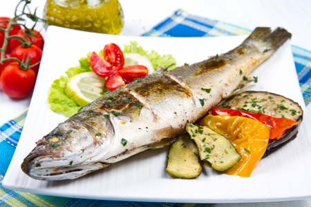 fish, sea bass grilled with lemon and grilled vegetables Фото со стока