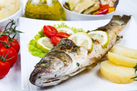 fish, sea bass grilled with lemon ,salad and potatoes photo