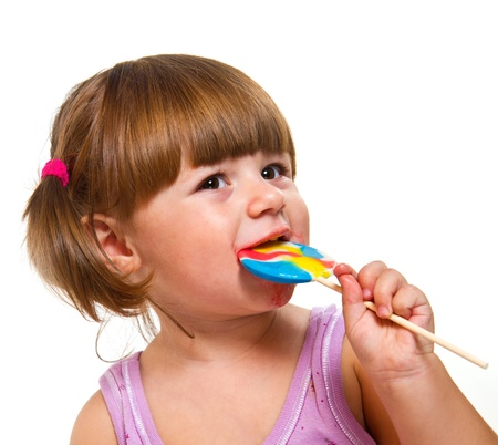 Cute little girl eating a colored lollipop  photo