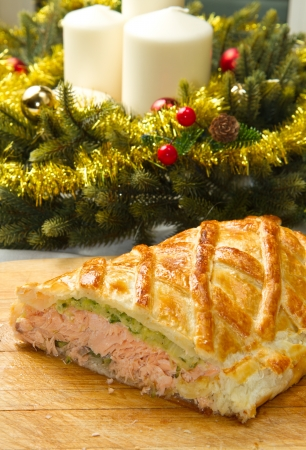 Traditional salmon in puff pastry with spinach and zucchini in christmas table  photo