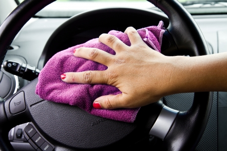 Womans hand with microfiber cloth polishing wheel of a car  photo