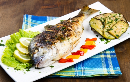 gilt head: Grilled gilt head sea bream on plate with lemon ,salad and grilled vegetables