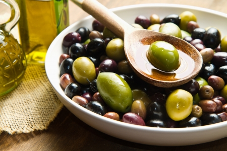Extra virgin healthy Olive oil with fresh olives on rustic wooden  photo