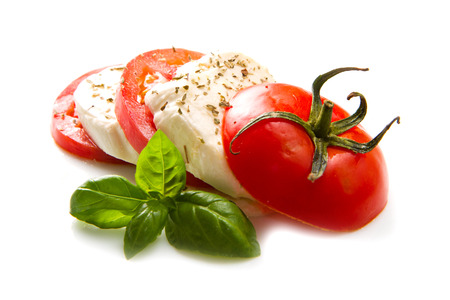 caprese salad: Tomato and mozzarella with basil leaves on white  Stock Photo