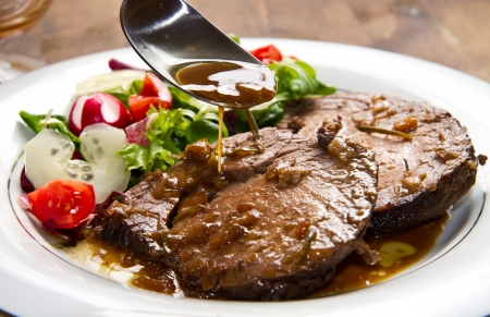 beef  garnished with fresh salad,  tomatoes, raddishes and cucumbers photo