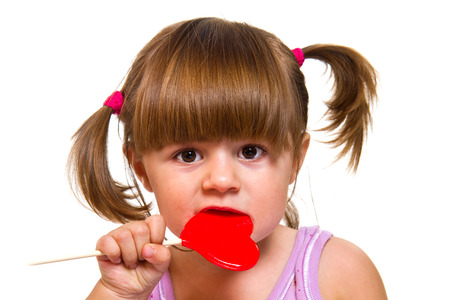 little girl eating red heart lollipop isolated on white photo